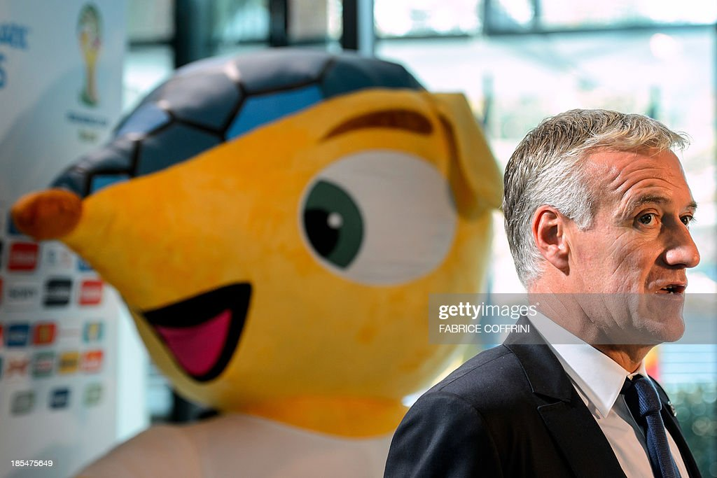 France's national football team coach Didier Deschamps answers journalists' questions on October 21, 2013 next to the mascot of the FIFA World Cup 2014 after attending the draw for the 2014 FIFA World Cup European zone play-off matches held at the headquarters of the football's world governing body in Zurich. The play-off matches are due to be played on November 15 and 19.