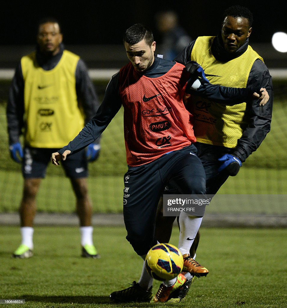 France's national football team forward Romain Alessandrini (C) controls the ball next to goakeeper Steve Mandanda (R) during a training session, on February 4, 2013 in in Clairefontaine-en-Yvelines, outside Paris, two days ahead a friendly football match France vs Germany.
