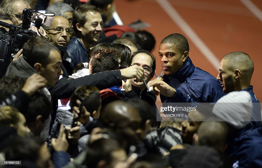 France's national football team forwards Loic Remy (C) and Karim Benzema (R) pose for pictures and sign autographs to supporters before a training session in Clairefontaine-en-Yvelines, outside Paris, on November 11, 2013, ahead of their two-legged World Cup 2014 qualifying play-off match against Ukraine. AFP PHOTO / FRANCK FIFE