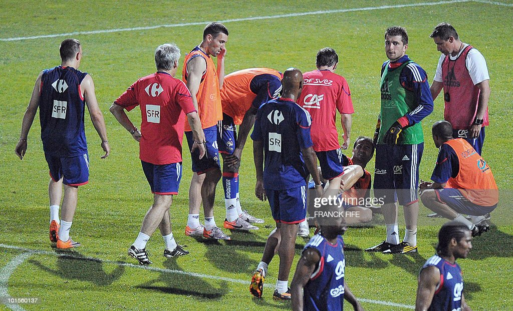 France's national football team players and staff members surround defender Marc Planus (4thR) during a training session, on June 2, 2010 in Saint-Pierre, on the French Indian Ocean island of La Reunion, as part of the preparation for the upcoming World Cup 2010. Planus has sprained his right ankle during the training session and his participation to France friendly scheduled against China in Reunion on June 4, 2010 is highly uncertain.