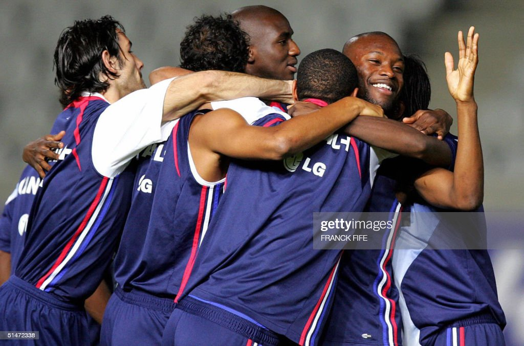 France's national football team players hug during a training session 12 October 2004 at the GSP Stadium in Nicosia on the eve of the World Cup 2006...