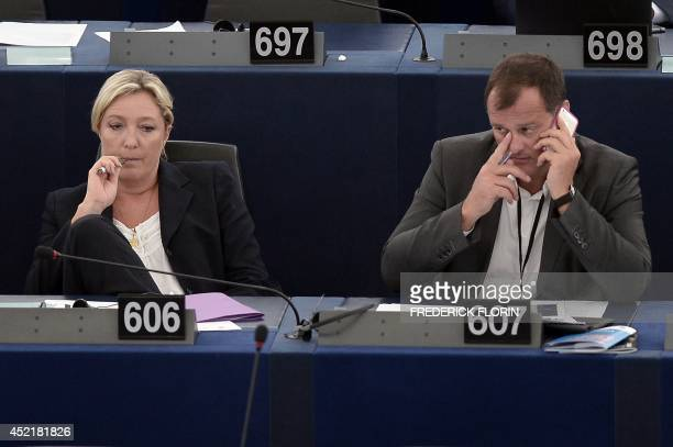 France's National Front political party head Marine Le Pen uses an electronic cigarette as she waits with her companion Louis Aliot for the results...