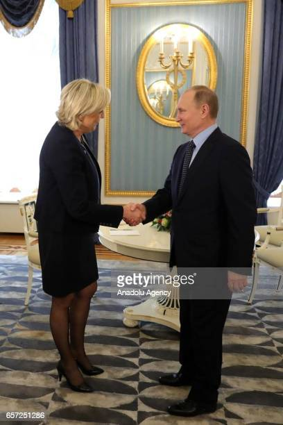 France's National Front President Marine Le Pen and Russian President Vladimir Putin shake hands as they pose for a photograph before their meeting...