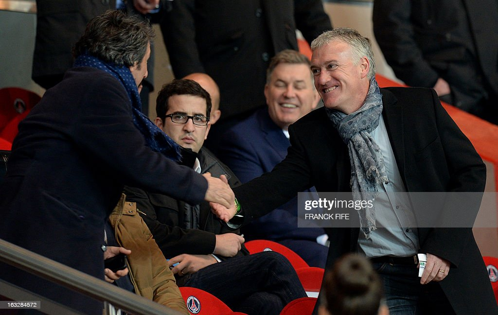France's national head coach Didider Deschamps (R) shakes hands with French actor Richard Anconina before the UEFA Champions League round of 16 second leg football match between Paris Saint-Germain and Valencia at the Parc des Princes stadium in Paris, on March 6, 2013.