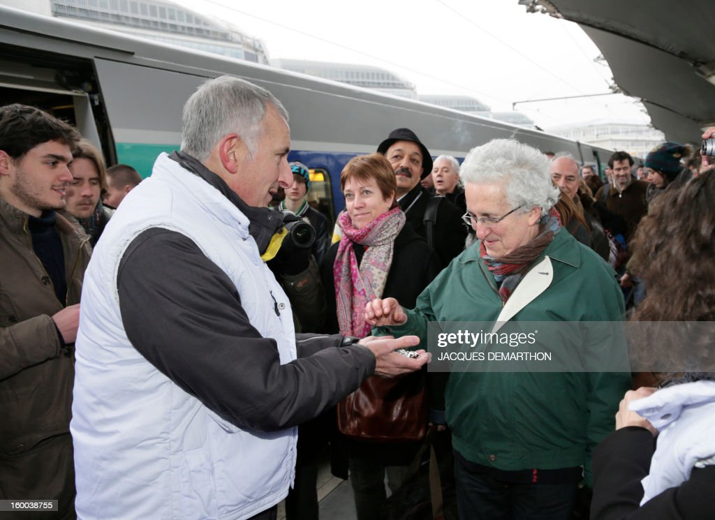 France's national rail company SNCF head, Guillaume Pepy (L), distributes chocolates at the Gare de Lyon railways station on January 25, 2013 in Paris, to celebrate the 2 billionth traveler of the company.
