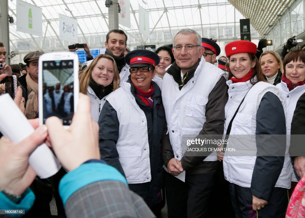 France's national rail company SNCF head, Guillaume Pepy (C), poses with employees at the Gare de Lyon railways station on January 25, 2013 in Paris, to celebrate the 2 billionth traveler of the company.