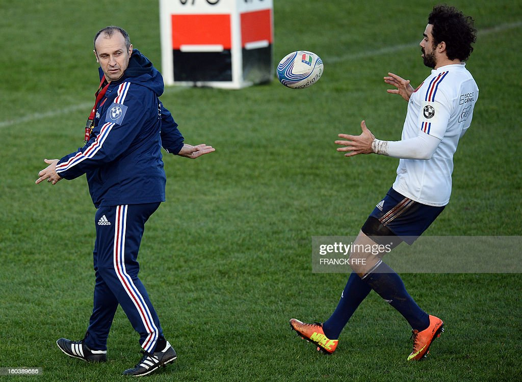 France's national rugby union team head coach Philippe Saint Andre (L) passes the ball to wing Yoann Huget during a training session, on January 30, 2013, in Marcoussis, south of Paris, in preparation of the Six Nations rugby union tournament. France will play against Italy in a 2013 six nations' rugby match on February 3, 2013. AFP PHOTO / FRANCK FIFE