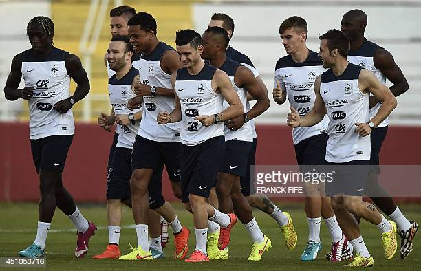 France's national team players warm up during a training session at the Santa Cruz Stadium in Ribeirao Preto on June 22 during the 2014 FIFA World...