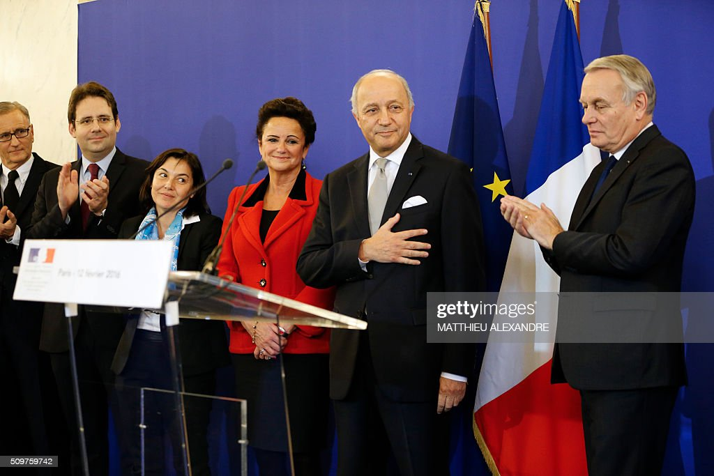 France's newly appointed French Foreign Minister Jean-Marc Ayrault (R) applauds France's outgoing Foreign Minister Laurent Fabius (2ndR) on February 12, 2016 in Paris, during the handover ceremony. French President Francois Hollande reshuffled his cabinet on February 11, 2016, naming Jean-Marc Ayrault foreign minister and adding several ecologists to government as he seeks to widen his political base ahead of a presidential poll in 2017. ALEXANDRE