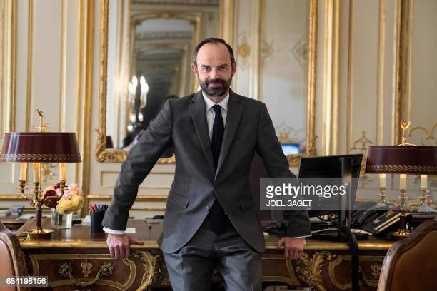 France's newly appointed Prime Minister Edouard Philippe poses in his office at Matignon on May 17 2017 in Paris / AFP PHOTO / Joël SAGET