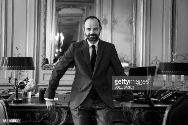 France's newly appointed Prime Minister Edouard Philippe poses in his office at Matignon on May 17 2017 in Paris / AFP PHOTO / joel SAGET