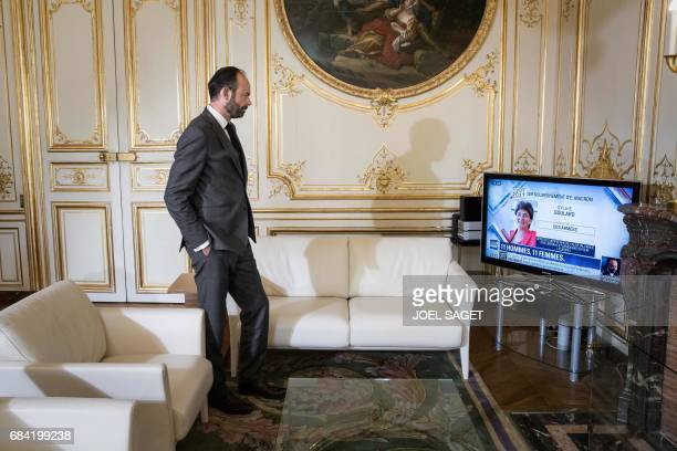 TOPSHOT France's newly appointed Prime Minister Edouard Philippe watches the unveiling of the French government on TV as he poses in his office at...