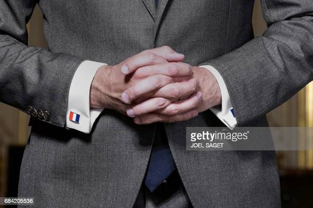 France's newly appointed Prime Minister Edouard Philippe wearing a set of cufflinks in the colors of the French national flag poses in his office at...