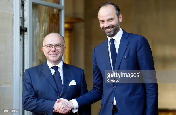 France's newlyappointed Prime Minister Edouard Philippe and outgoing Prime Minister Bernard Cazeneuve shake hands during the official handover...