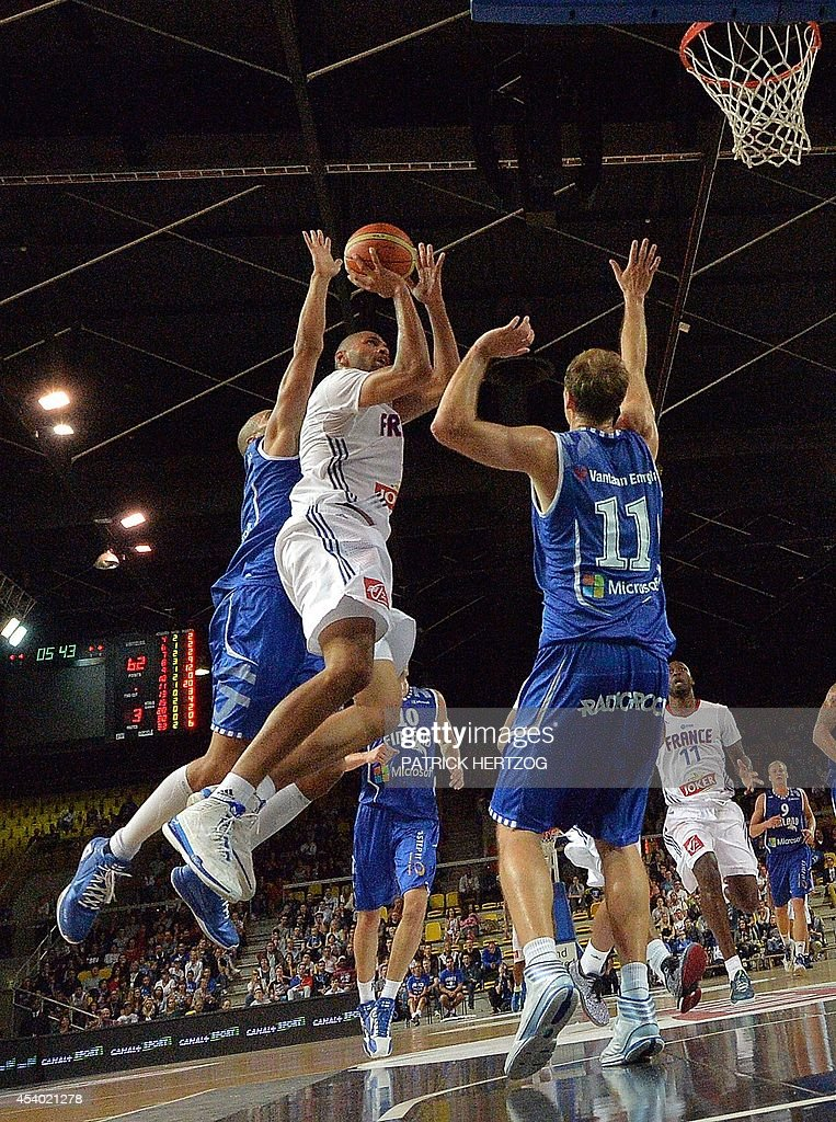 France's Nicolas Batum (C) jumps to score past Finland's defenders during a friendly basketball match between France and Finland in Strasbourg, eastern France, on August 23, 2014 ahead of 2014 FIBA Basketball World Cup.