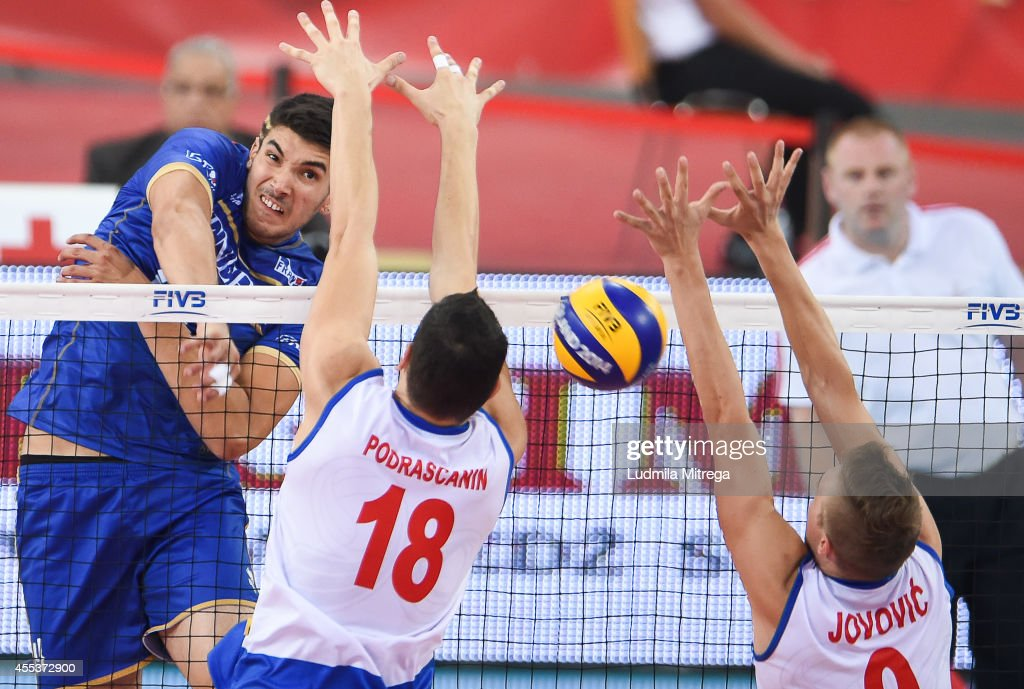 France's Nicolas Le Goff attacks against Serbia's Marko Podrascanin and Nikola Jovovic during the FIVB World Championships match between Serbia and...