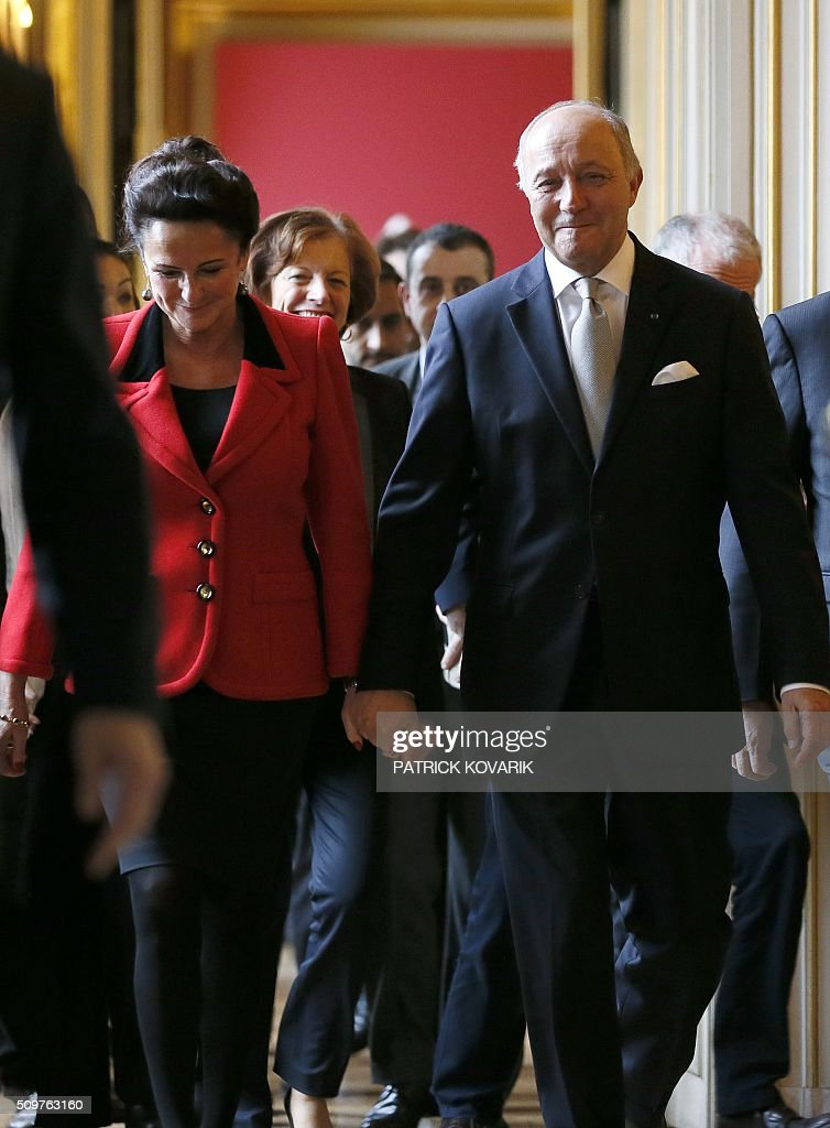 France's outgoing Foreign Minister Laurent Fabius (R) and his companion Marie-France Marchand-Baylet leave following the handover ceremony at the Foreign Ministry on February 12, 2016 in Paris. French President Francois Hollande reshuffled his cabinet on February 11, 2016, naming Jean-Marc Ayrault foreign minister and adding several ecologists to government as he seeks to widen his political base ahead of a presidential poll in 2017. / AFP / PATRICK KOVARIK