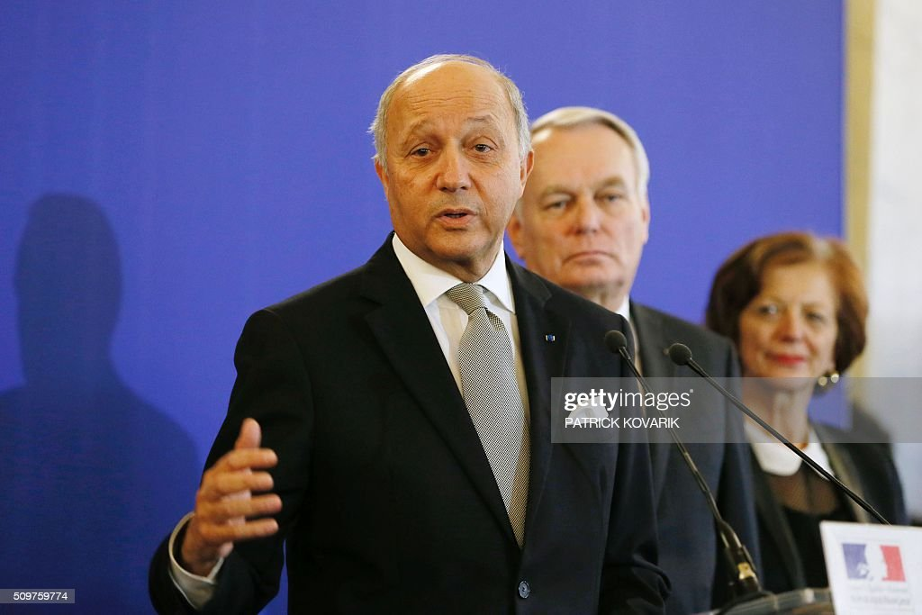 France's outgoing Foreign Minister Laurent Fabius (Front) delivers a speech as newly appointed French Foreign Minister Jean-Marc Ayrault (Rear C) listens during the handover ceremony on February 12, 2016 in Paris. French President Francois Hollande reshuffled his cabinet on February 11, 2016, naming Jean-Marc Ayrault foreign minister and adding several ecologists to government as he seeks to widen his political base ahead of a presidential poll in 2017. / AFP / PATRICK KOVARIK