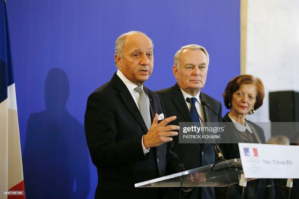 France's outgoing Foreign Minister Laurent Fabius (L) delivers a speech as newly appointed French Foreign Minister Jean-Marc Ayrault (C) listens during the handover ceremony on February 12, 2016 in Paris. French President Francois Hollande reshuffled his cabinet on February 11, 2016, naming Jean-Marc Ayrault foreign minister and adding several ecologists to government as he seeks to widen his political base ahead of a presidential poll in 2017. / AFP / PATRICK KOVARIK