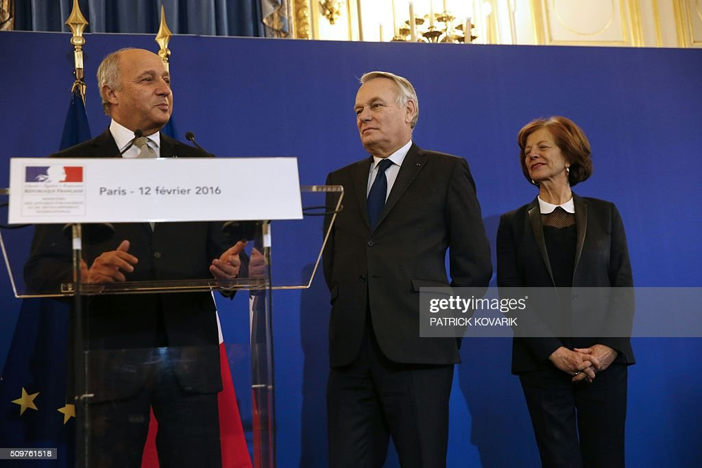 France's outgoing Foreign Minister Laurent Fabius (L) delivers a speech as newly appointed French Foreign Minister Jean-Marc Ayrault (2nd R) and his Brigitte listen during the handover ceremony on February 12, 2016 in Paris. French President Francois Hollande reshuffled his cabinet on February 11, 2016, naming Jean-Marc Ayrault foreign minister and adding several ecologists to government as he seeks to widen his political base ahead of a presidential poll in 2017. / AFP / PATRICK KOVARIK