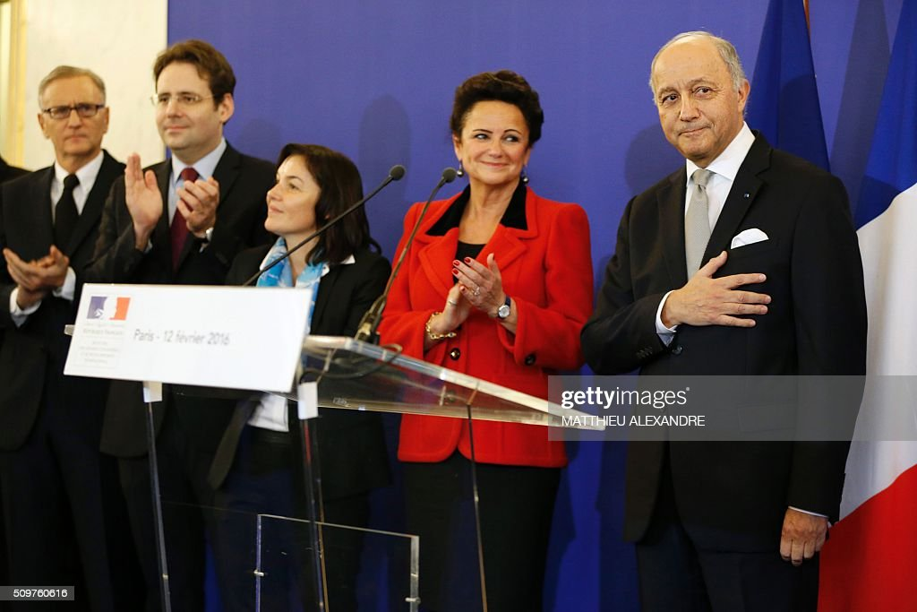 France's outgoing Foreign Minister Laurent Fabius (R) is applauded on February 12, 2016 in Paris, during the handover ceremony with France's newly appointed minister. French President Francois Hollande reshuffled his cabinet on February 11, 2016, naming Jean-Marc Ayrault foreign minister and adding several ecologists to government as he seeks to widen his political base ahead of a presidential poll in 2017. ALEXANDRE