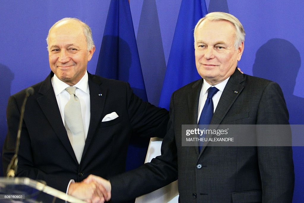France's outgoing Foreign Minister Laurent Fabius (L) shakes hands with newly appointed French Foreign Minister Jean-Marc Ayrault on February 12, 2016 in Paris, during the handover ceremony. French President Francois Hollande reshuffled his cabinet on February 11, 2016, naming Jean-Marc Ayrault foreign minister and adding several ecologists to government as he seeks to widen his political base ahead of a presidential poll in 2017. ALEXANDRE