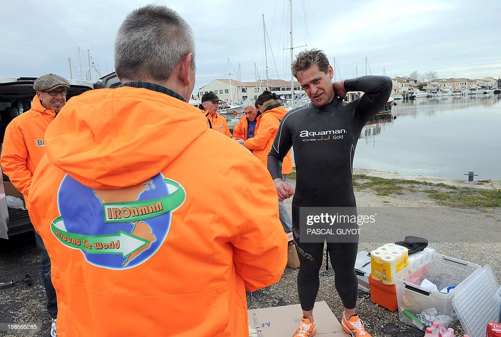 France's Pascal Pich, five times world ultra triathlon champion puts on his wetsuit at Aigues Mortes on December 19, 2012 at the start the French leg of his adventure. Pich is aiming to do in a year and on each continent a double Ironman, (7,6km swim, 360km cycle and 84km run) and a Deca Ironman (38km swim, 1800km cycle and 423 run). GUYOT