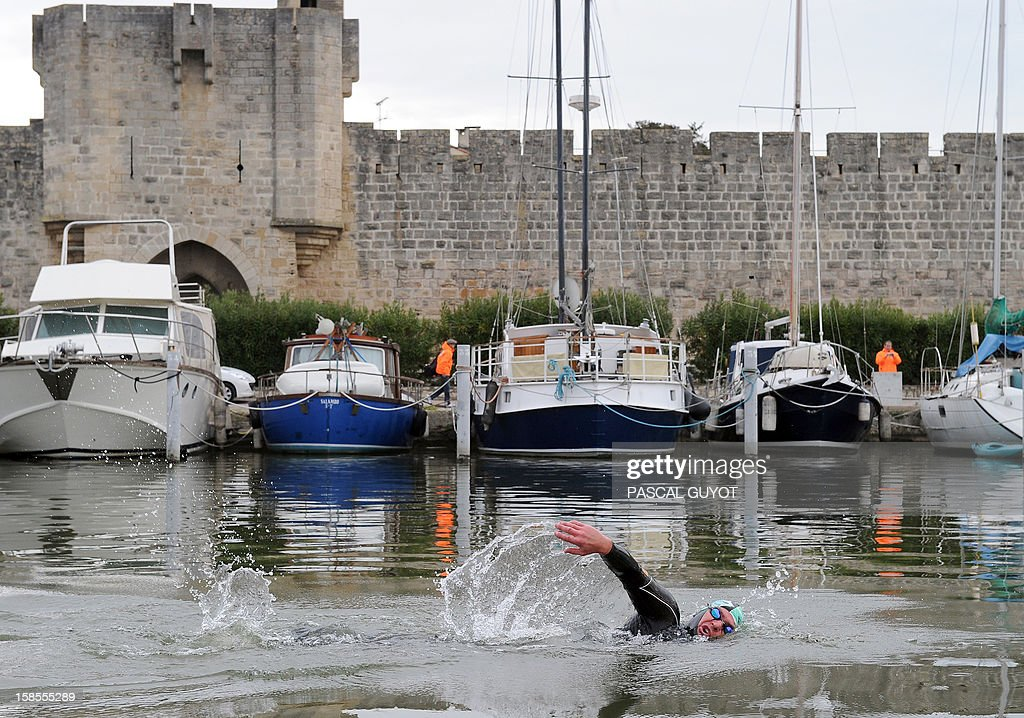 France's Pascal Pich, five times world ultra triathlon champion swims in the Rhome Canal at Aigues Mortes on December 19, 2012 at the start of the French leg of his adventure. Pich is aiming to do in a year and on each continent a double Ironman, (7,6km swim, 360km cycle and 84km run) and a Deca Ironman (38km swim, 1800km cycle and 423 run). GUYOT
