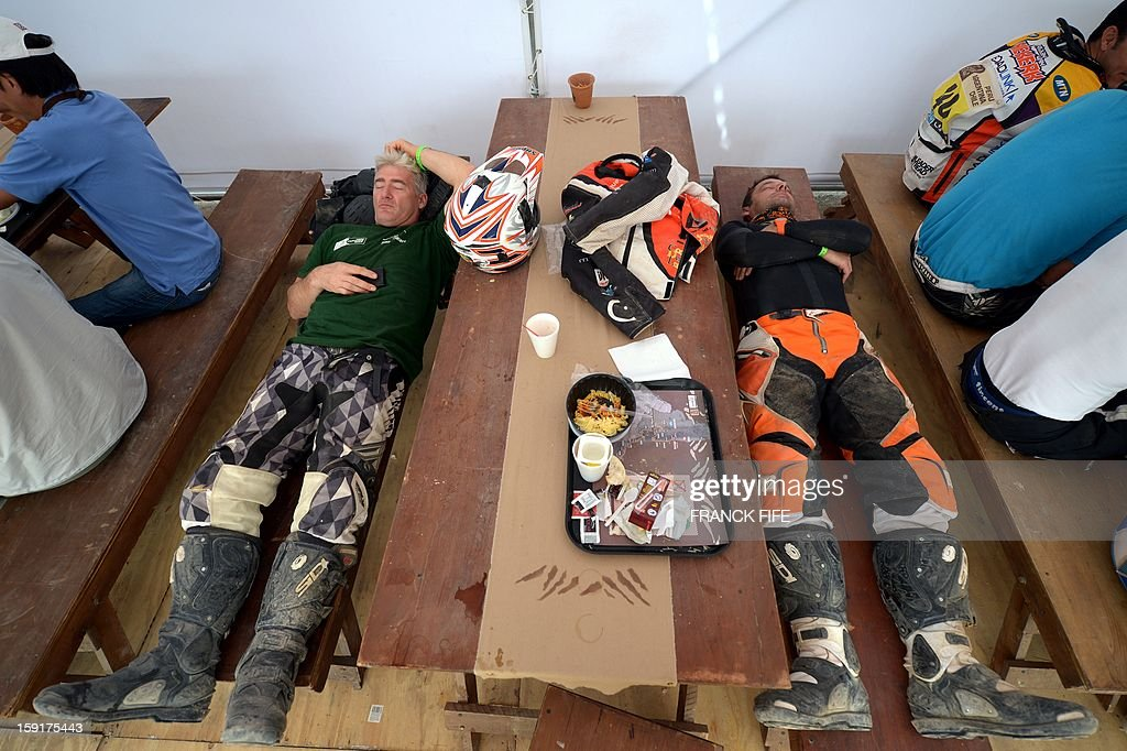 France's Patrice Carillon (R) and an unidentified biker sleep during the breakfast before the Stage 5 of the Dakar 2013 between Nazca and Arequipa, Peru, on January 9, 2013. The rally takes place in Peru, Argentina and Chile from January 5 to 20.