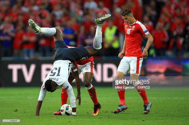 France's Paul Pogba goes head first over Switzerland's Breel Embolo as Switzerland's Granit Xhaka looks on as they battle for the ball