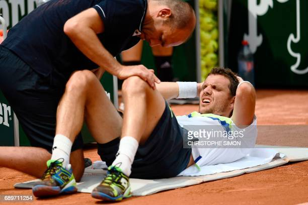 France's PaulHenri Mathieu receives medical attention during his tennis match against Belgium's David Goffin at the Roland Garros 2017 French Open on...