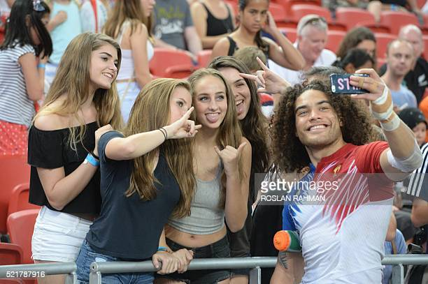France's Pierre Gilles Lakafia takes a selfie with fans during the Singapore Sevens rugby tournament on April 17 2016 / AFP / Roslan RAHMAN