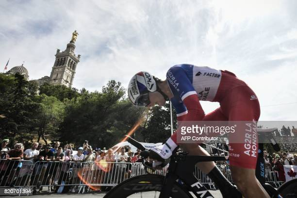 France's PierreRoger Latour rides past the NotreDame de la Garde basilica as he competes in a 225 km individual timetrial the twentieth stage of the...