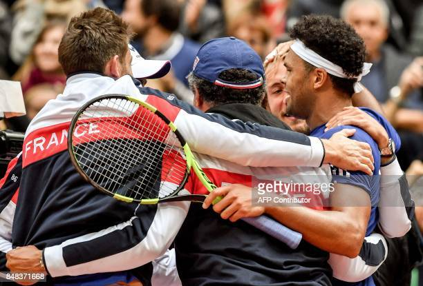 France's player JoWilfried Tsonga hugs teammates as he celebrates after winning the Davis Cup World Group semifinal tennis match against Serbia at...