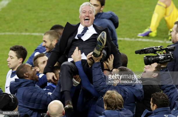 France's players carry coach Didier Deschamps as they celebrate after winning the 2014 World Cup qualifying playoff second leg football match between...