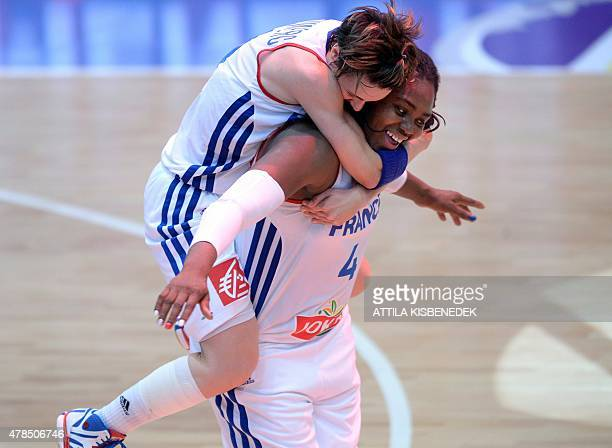 France's players Isabelle Yacoubou and Celine Dumerc celebrate their victory over Russia after the final round basketball match between France and...