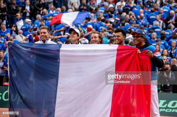 France's players Nicolas Mahut PierreHugues Herbert Lucas Pouille JoWilfried Tsonga and captain Yannick Noah hold a French flag after Tsonga fought...
