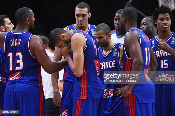 France's point guard Tony Parker and his teammates react after losing to Spain in the semifinal basketball match between Spain and France at the...