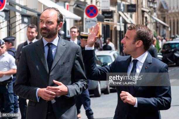 France's President Emmanuel Macron accompanied by Prime Minister Edouard Philippe waves on his way to sign a book of condolences at the British...