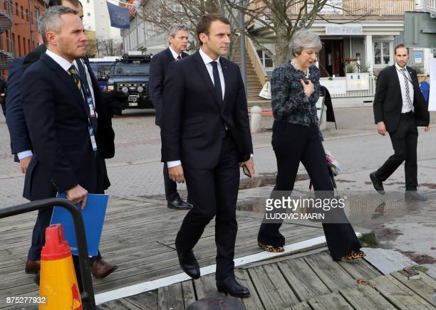 France's President Emmanuel Macron and Britain's Prime Minister Theresa May talk as members of the European delegations head out for a lunch break...