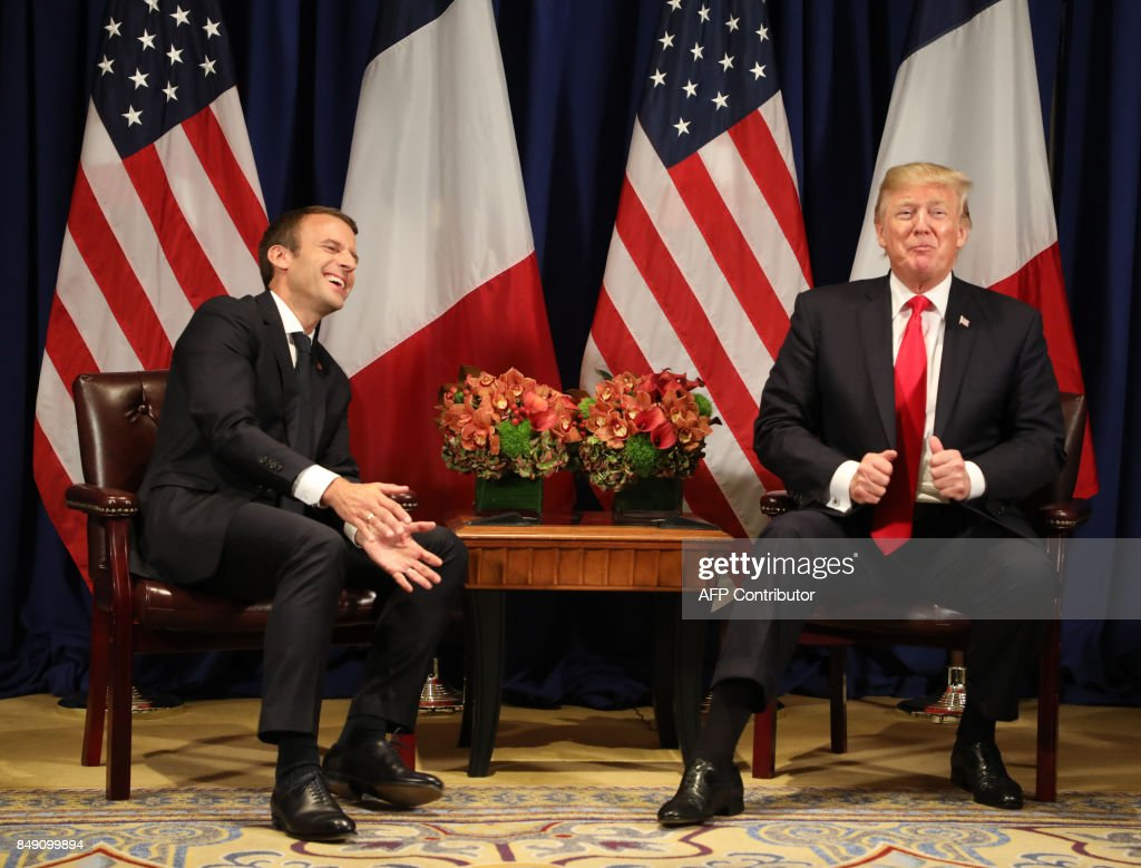 TOPSHOT - France's president Emmanuel Macron (L) laughs with US President Donald Trump before a meeting at the Palace Hotel during the 72nd session of the United Nations General Assembly on September 18, 2017, in New York. / AFP PHOTO / ludovic MARIN