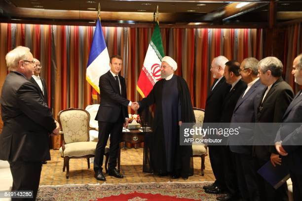 France's President Emmanuel Macron shakes hands with his Iranian counterpart Hassan Rouhani as Iran's foreign minister Mohammad Javad Zarif and other...