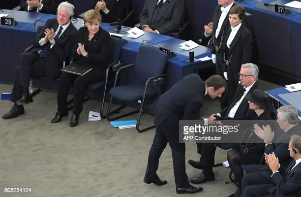 France's President Emmanuel Macron shakes hands with the widow of former German Chancellor Helmut Kohl Maike KohlRichter as US former President Bill...