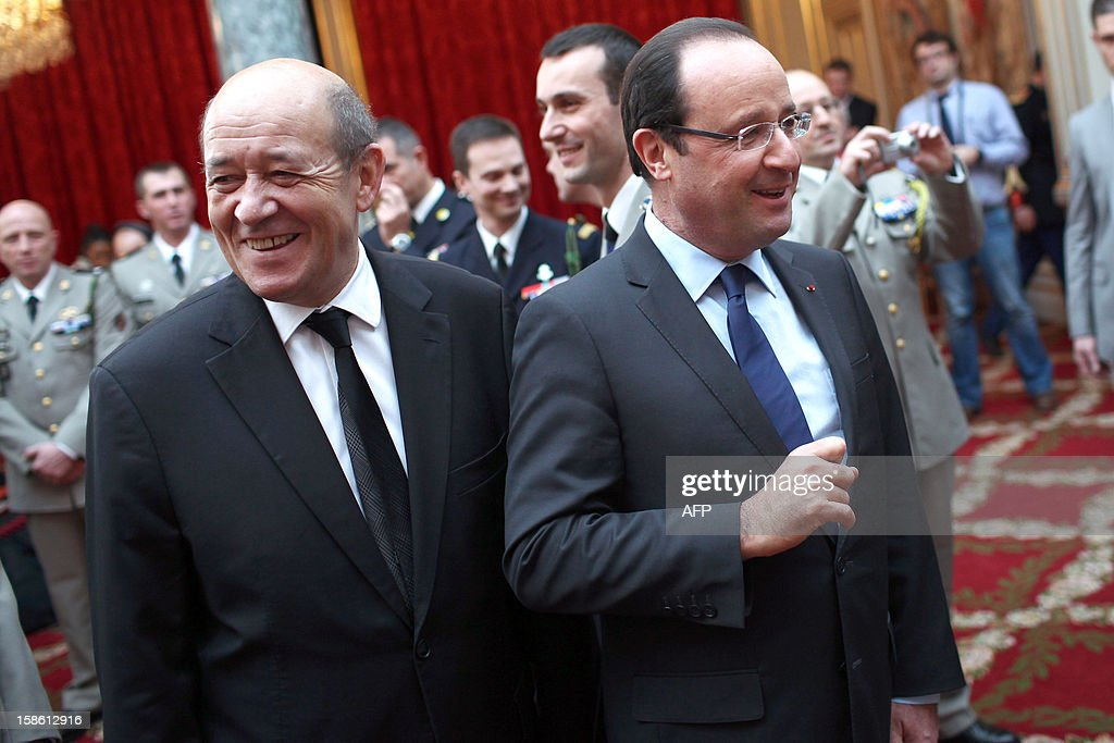 France's President Francois Hollande (R) and Defence minister Jean-Yves Le Drian take part in a ceremony in honour of French troops that served in Afghanistan, on December 21, 2012 at the Elysee Palace, in Paris. Hollande has declared 'mission accomplished' for French combat troops who returned home recently from Afghanistan. France still has 1,500 troops in Afghanistan repatriating equipment or working in roles like providing medical care or helping run Kabul's airport. Hollande said the numbers will decline to 500 by mid-2013. AFP PHOTO POOL THIBAULT CAMUS