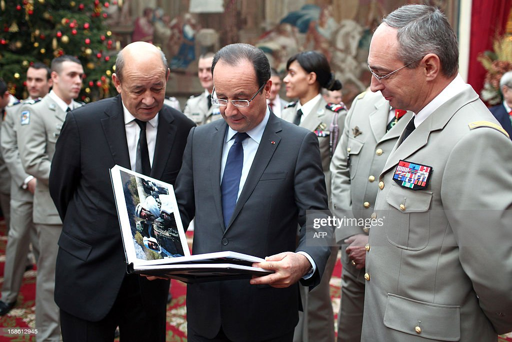 France's President Francois Hollande (C) and France's Defense Minister Jean-Yves Le Drian (L) take a look at a book offered by French army General Eric Hautecloque Raysz (R) during a ceremony in honour of French troops that served in Afghanistan, on December 21, 2012 at the Elysee Palace, in Paris. Hollande has declared 'mission accomplished' for French combat troops who returned home recently from Afghanistan. France still has 1,500 troops in Afghanistan repatriating equipment or working in roles like providing medical care or helping run Kabul's airport. Hollande said the numbers will decline to 500 by mid-2013.