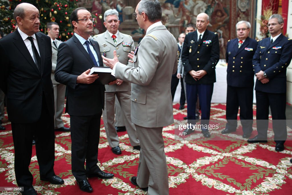 France's President Francois Hollande (2ndL) and France's Defense Minister Jean-Yves Le Drian (L) speak with with French army General Eric Hautecloque-Raysz during a ceremony in honour of French troops that served in Afghanistan, on December 21, 2012 at the Elysee Palace, in Paris. Hollande has declared 'mission accomplished' for French combat troops who returned home recently from Afghanistan. France still has 1,500 troops in Afghanistan repatriating equipment or working in roles like providing medical care or helping run Kabul's airport. Hollande said the numbers will decline to 500 by mid-2013.