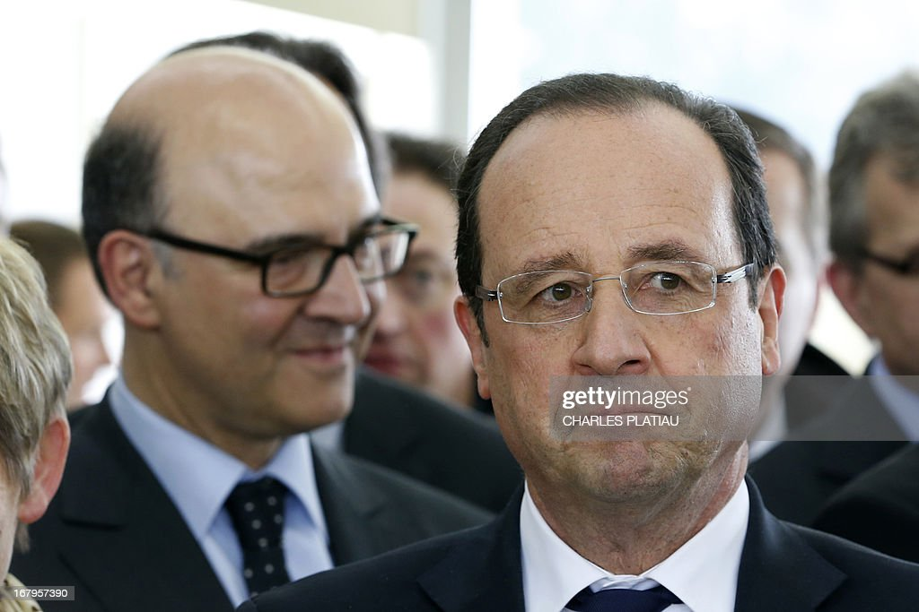 France's President Francois Hollande (R) and French Economy, Finance and Foreign Trade Minister Pierre Moscovici (L) visit a leather goods maker during a one-day visit focused on employment in rural areas in Avoudrey, eastern France, on May 3, 2013. POOL