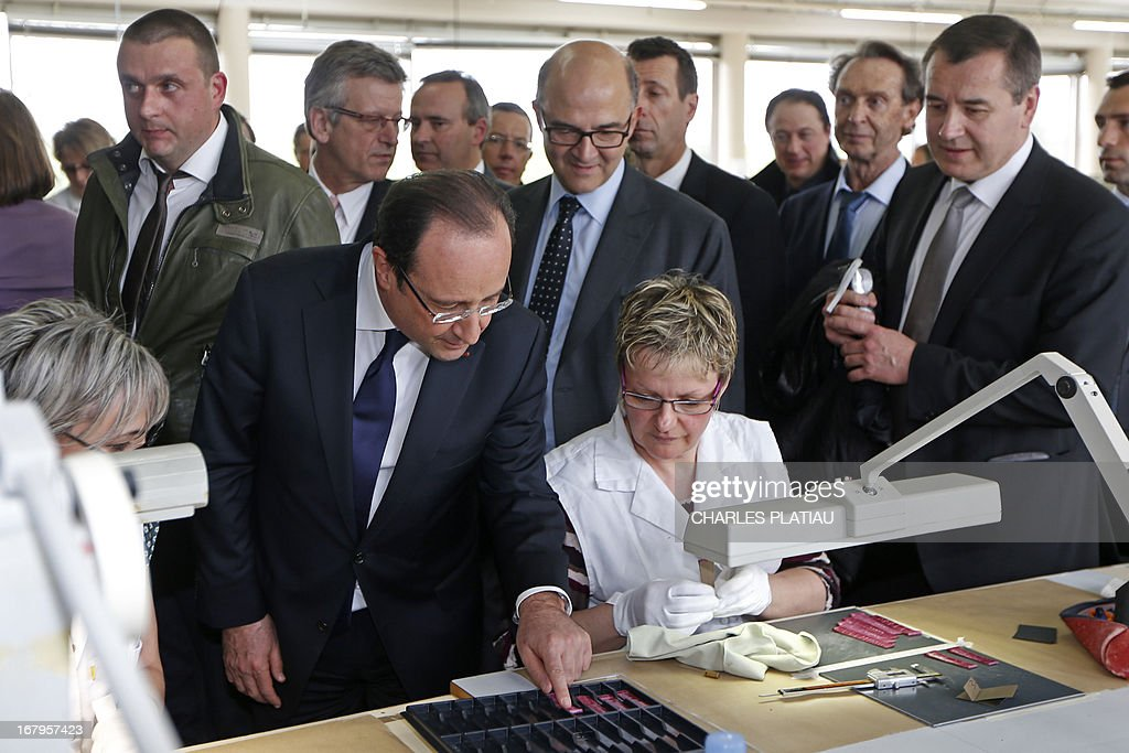 France's President Francois Hollande (L) and French Economy, Finance and Foreign Trade Minister Pierre Moscovici (C) visit a leather goods maker during a one-day visit focused on employment in rural areas in Avoudrey, eastern France, on May 3, 2013. POOL