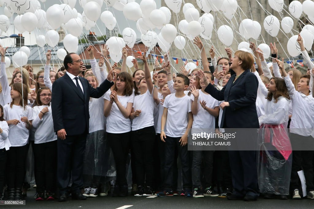 France's President Francois Hollande (L) and German Chancellor Angela Merkel (R) attend a ballon drop during a remembrance ceremony to mark the centenary of the battle of Verdun, in Verdun, on May 29, 2016. The battle of Verdun, in 1916, was one of the bloodiest episodes of World War I. The offensive which lasted 300 days claimed more than 300,000 lives. / AFP / POOL / Thibault Camus