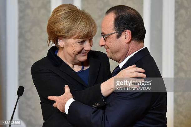 France's President Francois Hollande and German Chancellor Angela Merkel hug each other during a press conference after a summit aimed at ending 10...